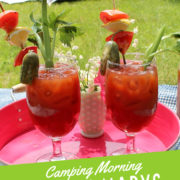 Tent in background of two bloody mary drinks in glasses