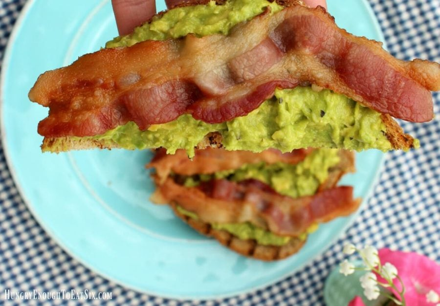Diagonal slice of toast with avocado and bacon strips