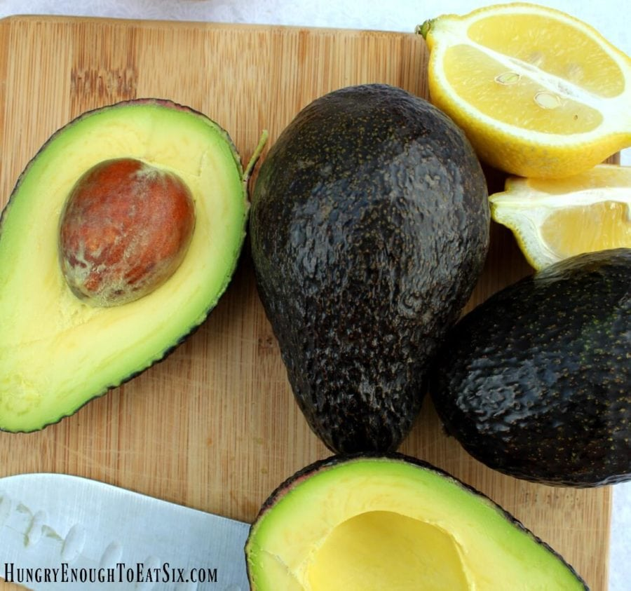 Sliced open avocados and lemon wedges