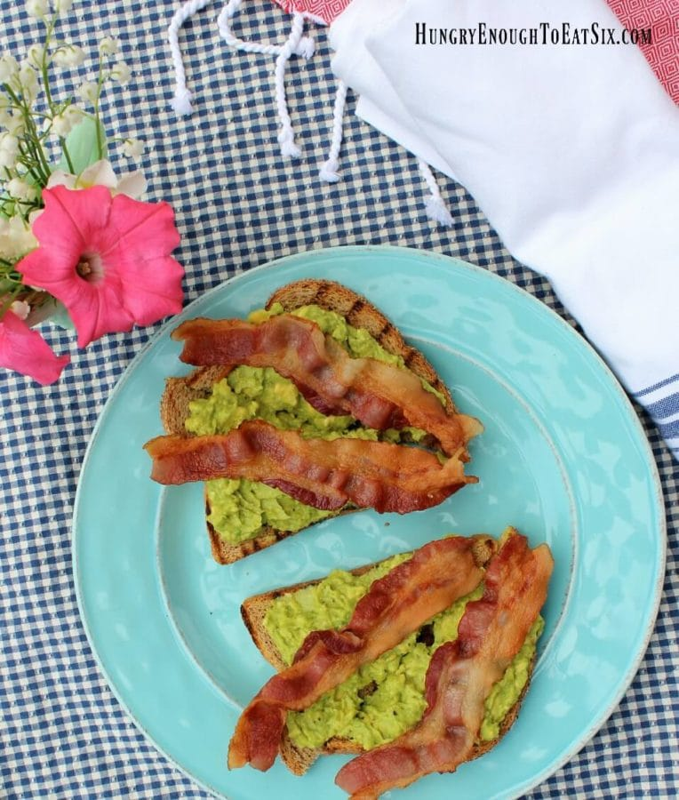 Blue plate with two slices of avocado spread toast with slices of bacon