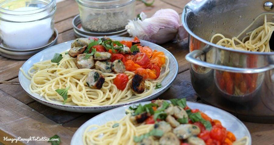 Pot of spaghetti next to two plates of pasta with tomato.