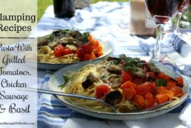 Image of plates of Fireside Pasta with Fresh Tomatoes, Basil and Chicken Sausage on an outdoor table for glamping