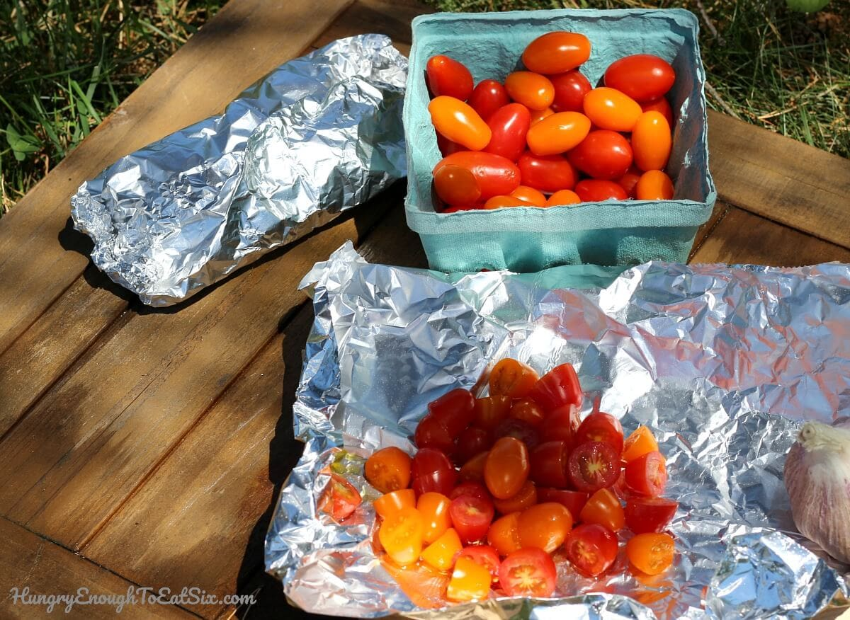 Image of sliced cherry tomatoes in foil packets