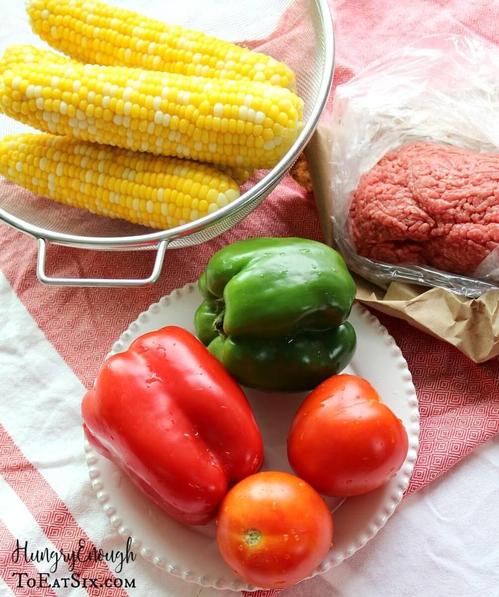 Image of whole peppers, corn, tomatoes, and a package of ground beef