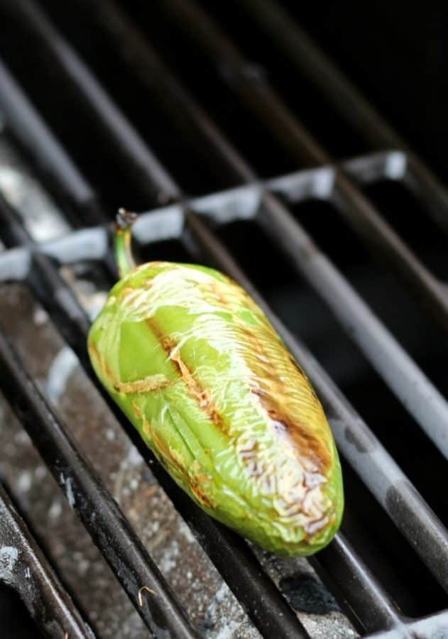 Charred whole jalapeno on grill grates.