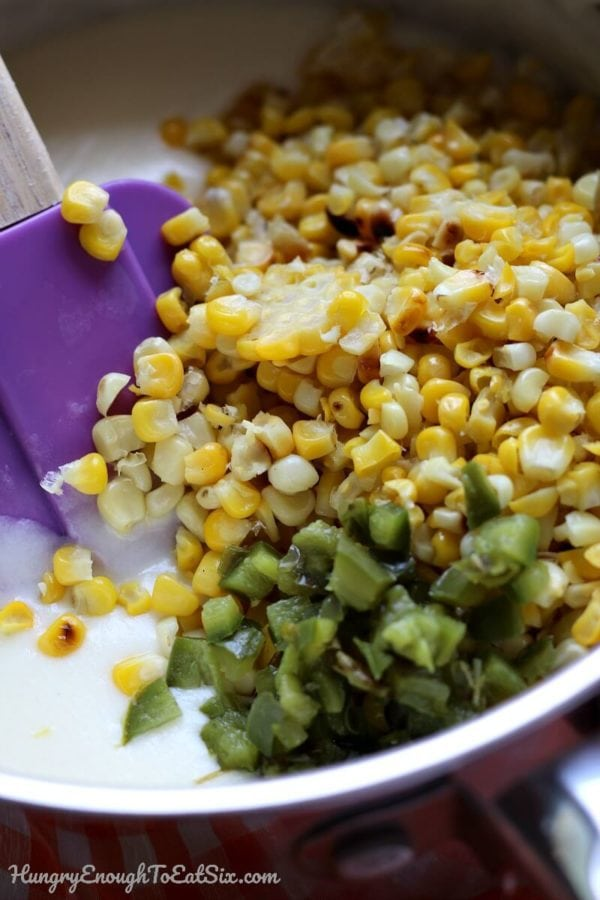 Grilled corn and chopped pepper getting stirred into cheese sauce.