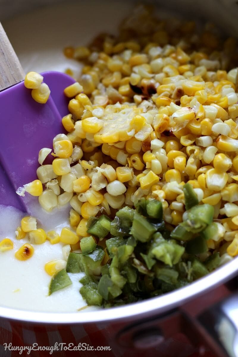 Image of diced jalapeno and grilled corn being stirred into queso sauce