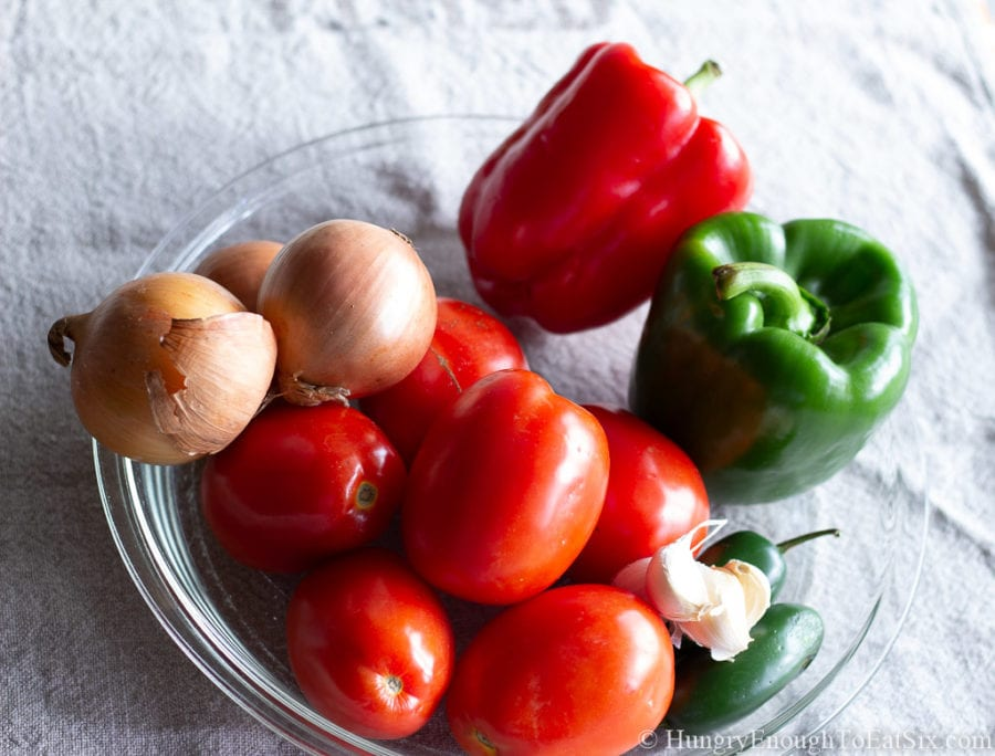 Image of bell peppers, onion, and tomatoes in a glass dish