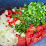 Image of chopped peppers, onions, and tomatoes in a stockpot