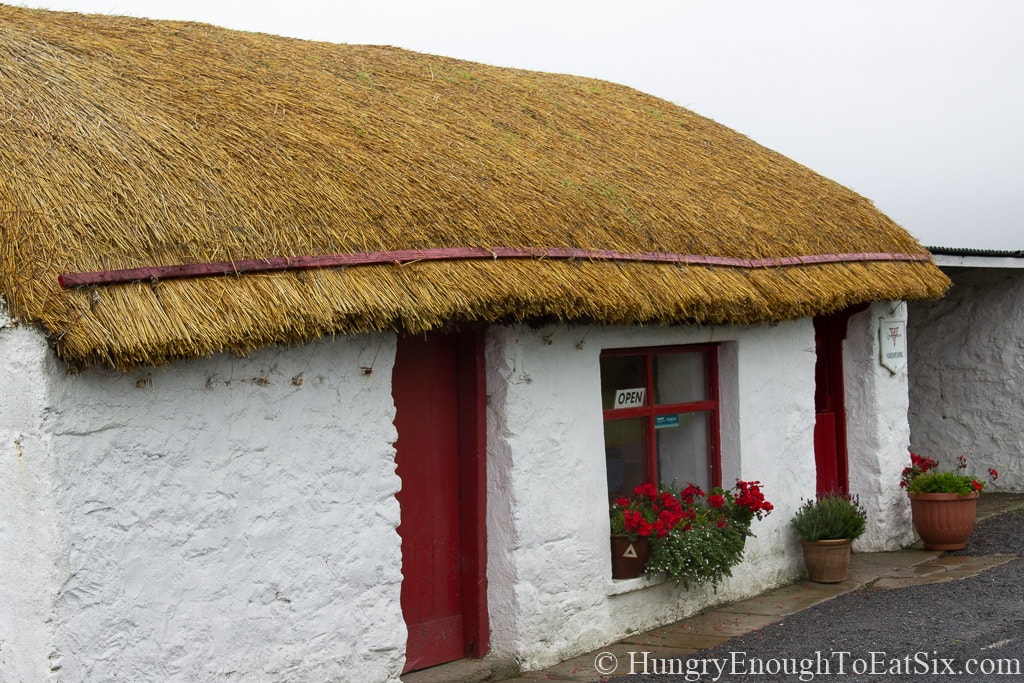 Image of a thatched cottage with a red door on St. John's Point, Donegal