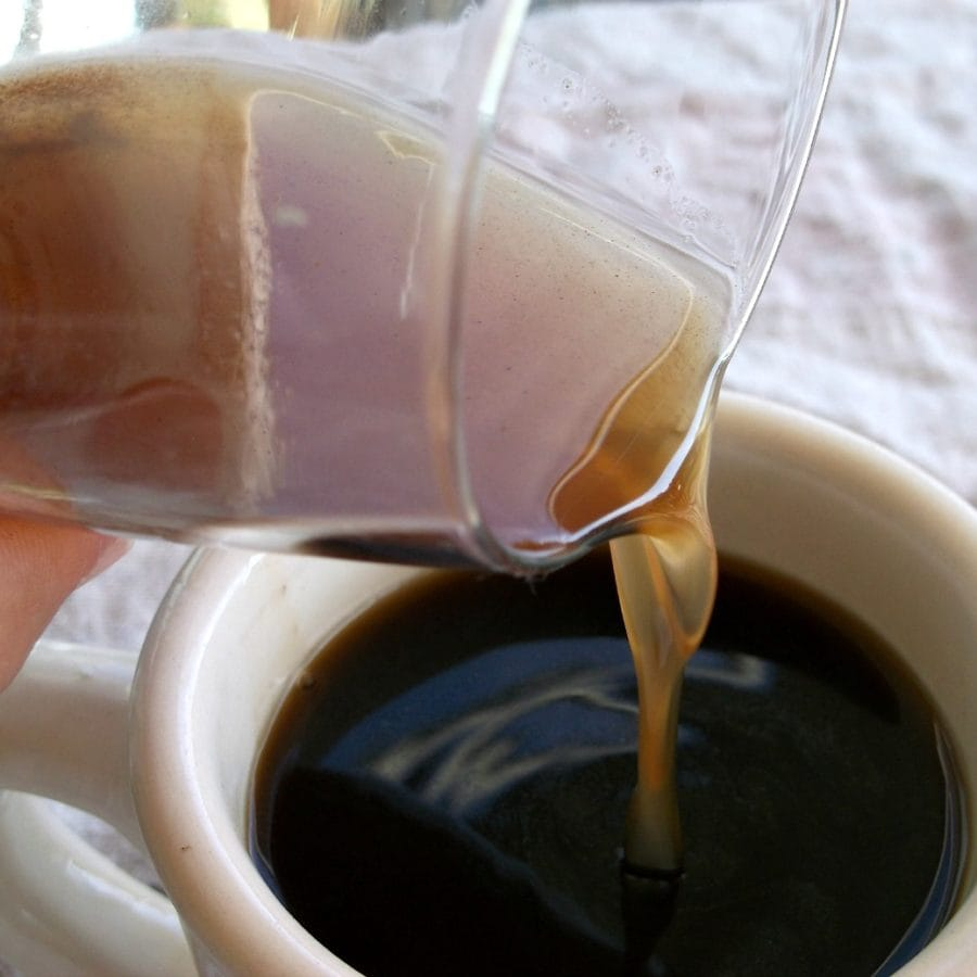 Image of Pumpkin Spice flavored syrup pouring into a cup of coffee