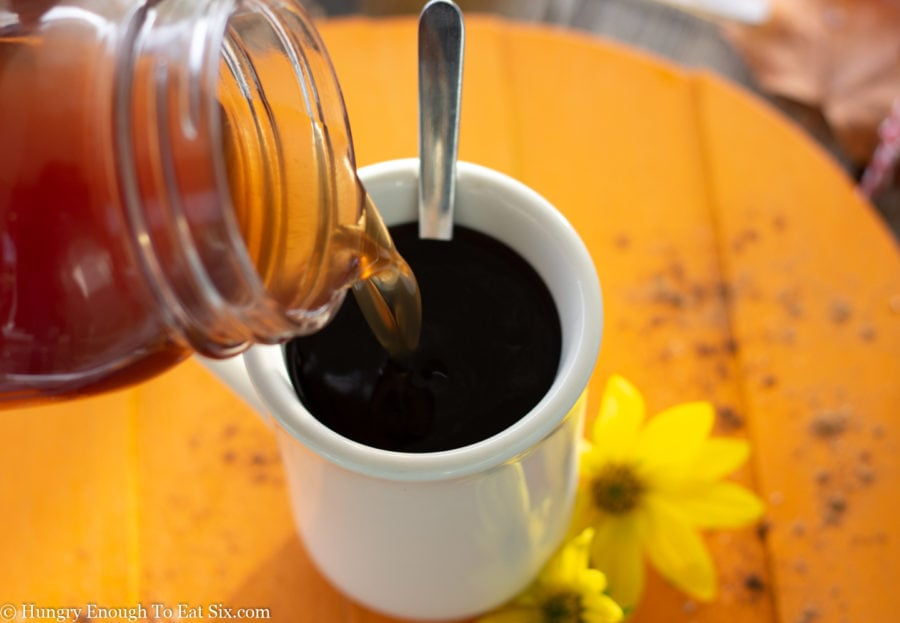 Clear brown syrup pouring into cup of coffee