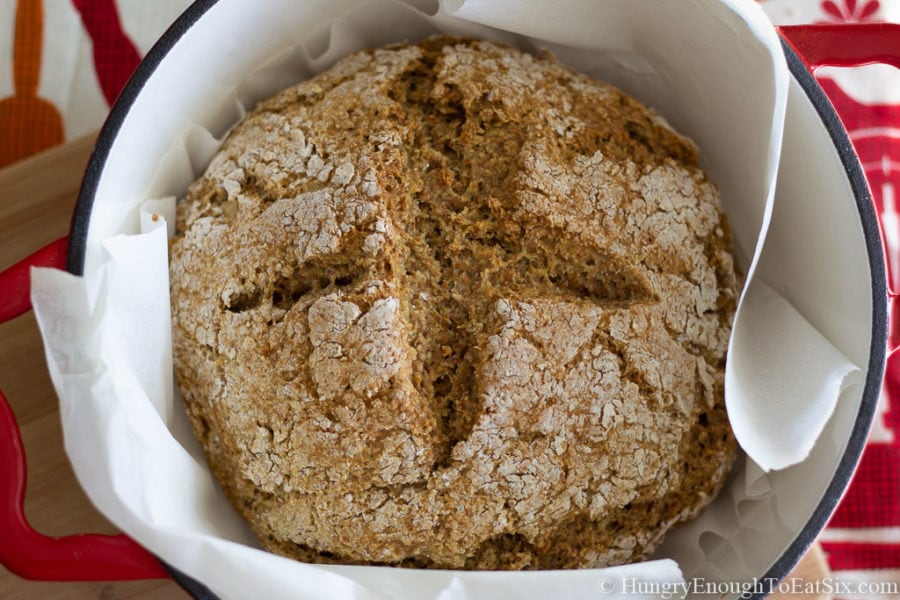 Round loaf of baked Irish brown bread in a Dutch oven.