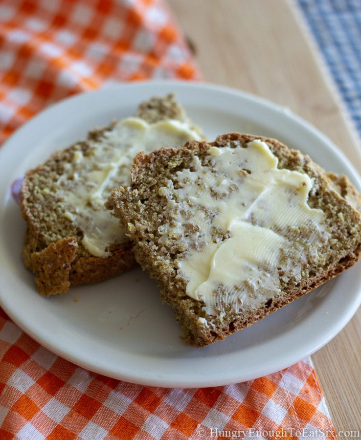 Brown Bread slices with butter on a white plate.