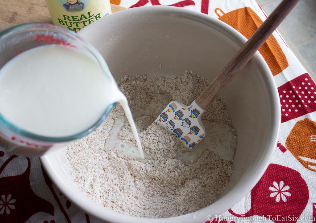 Bowl of coarse wholemeal flour with buttermilk being poured in.