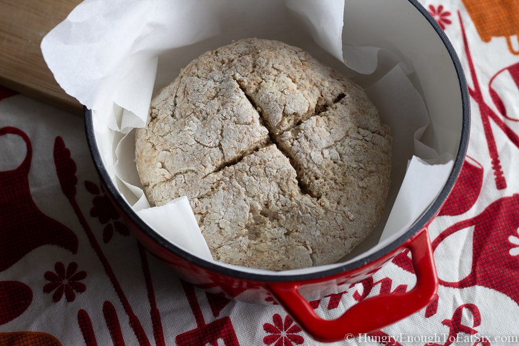 """Brown bread dough with an """"x"""" scored in the top of the dough."""