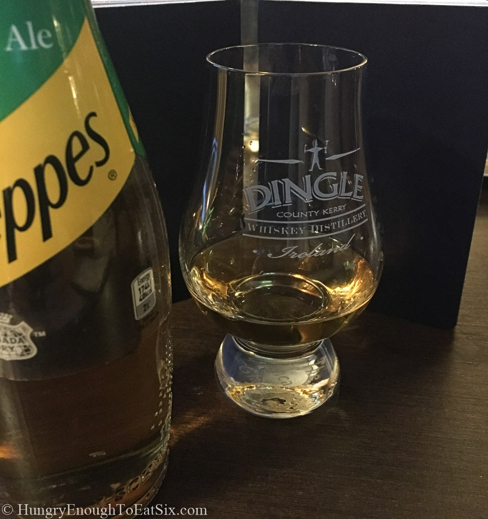 Small glass of Dingle Whiskey next to a bottle of Schweppes Ginger Ale.