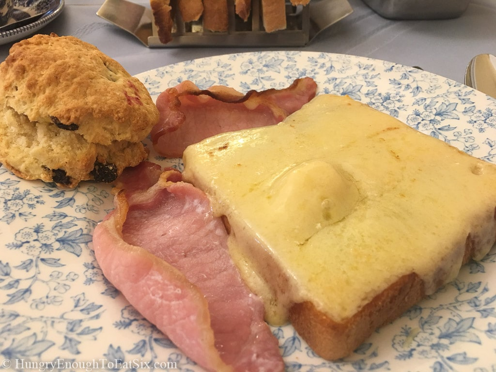 Breakfast plate of melted Cheddar on toast with Irish bacon and a biscuit.