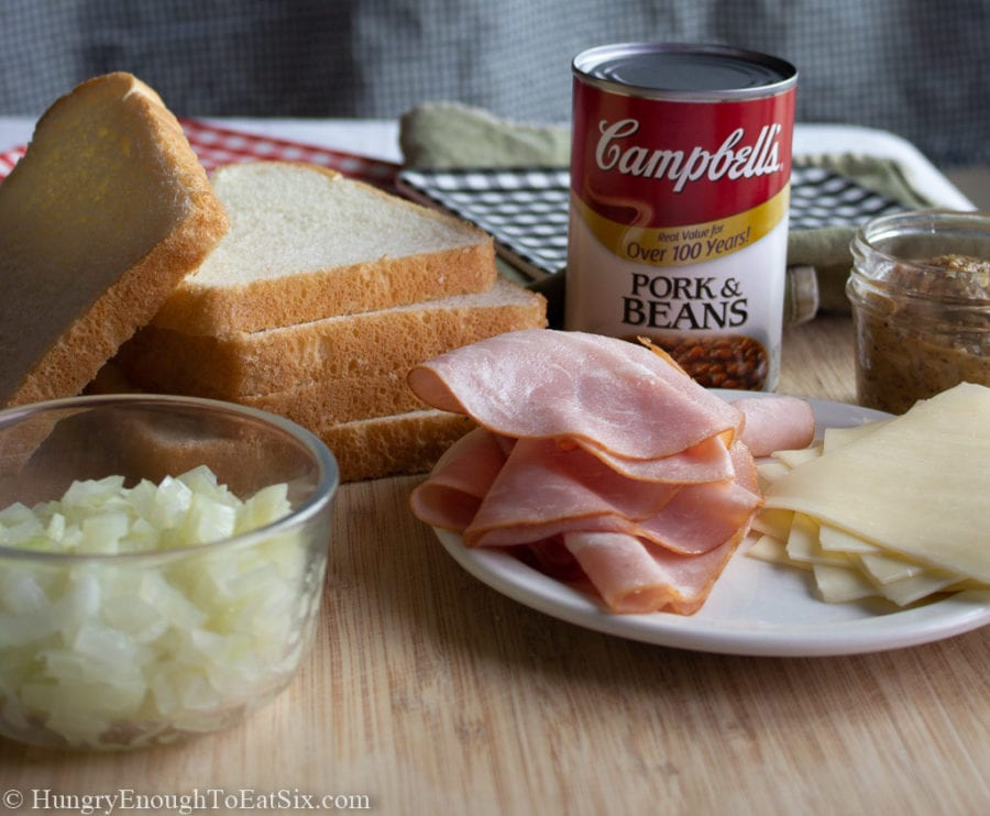 White bread slices, diced onion, slices of ham and cheese, and a can of pork & beans.