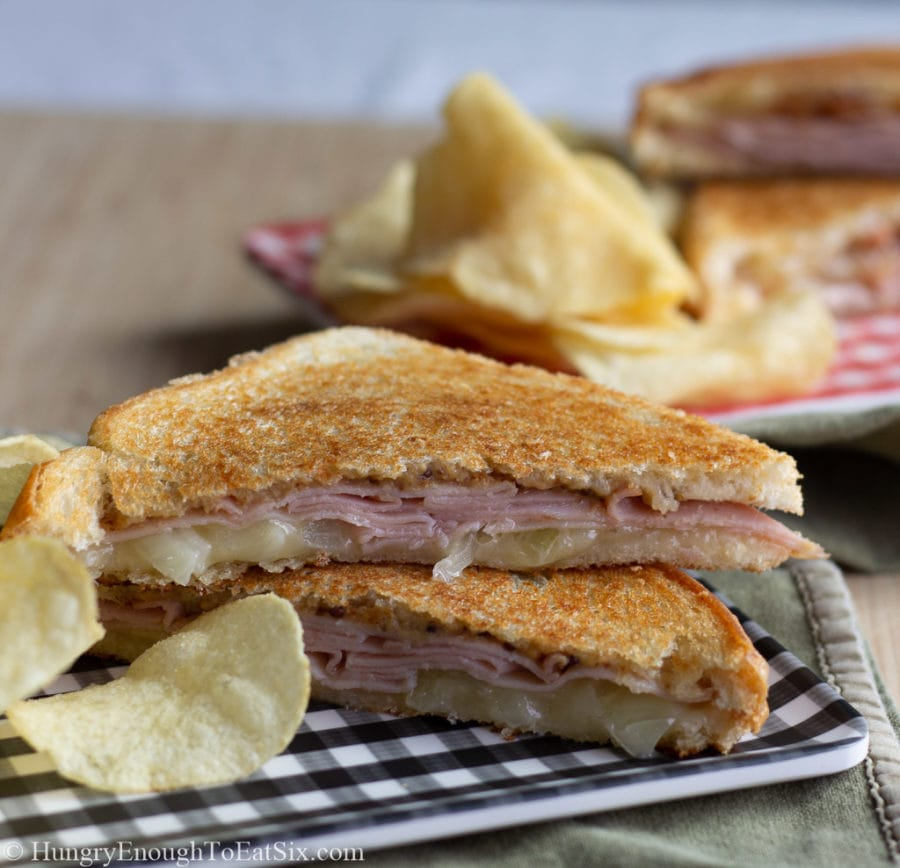 Two halves of a ham, onion and cheese toastie sandwich.