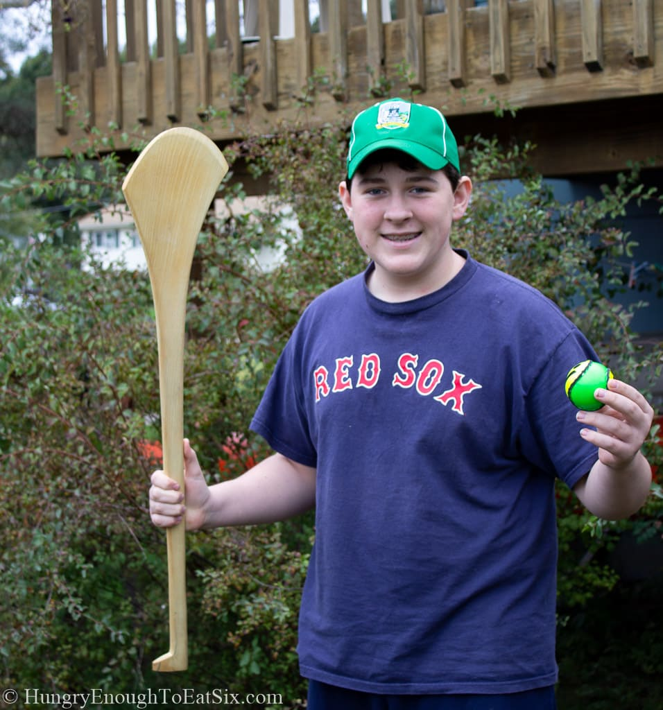 Young man holding a hurley and sliotar, equipment used in the game of hurling.