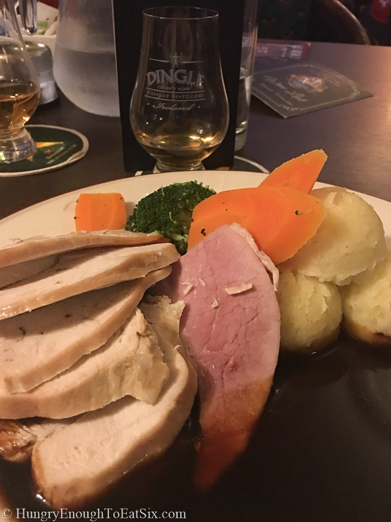 Irish roast dinner with slices of turkey and ham, carrots, potatoes and gravy.