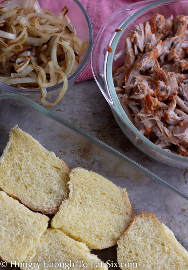 Bowls of seasoned shredded pork and sauteed onions next to slider roll bottoms in glass pan.