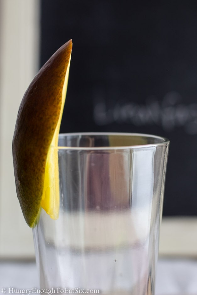Image of a mango on the rim of a glass