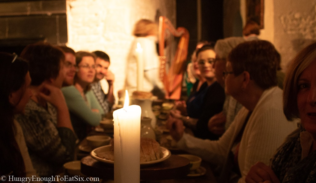 Image of people taking at long candlelit table at the medieval banquet, Bunratty Castle