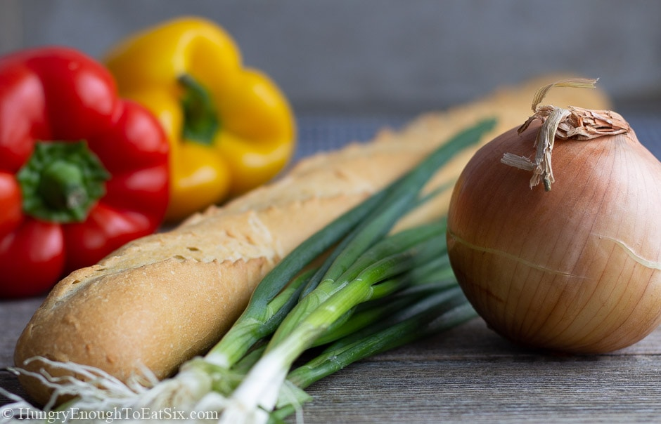 Image of red and yellow bell peppers, a baguette, scallions, and an onion.