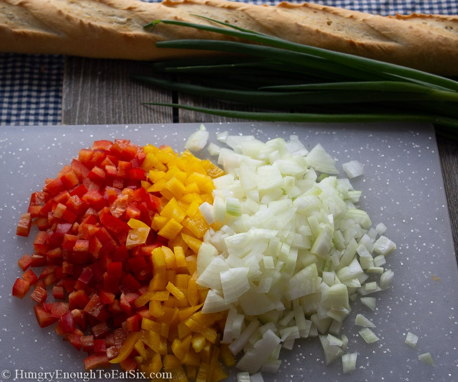 Image of diced red and yellow bell peppers and diced onion.