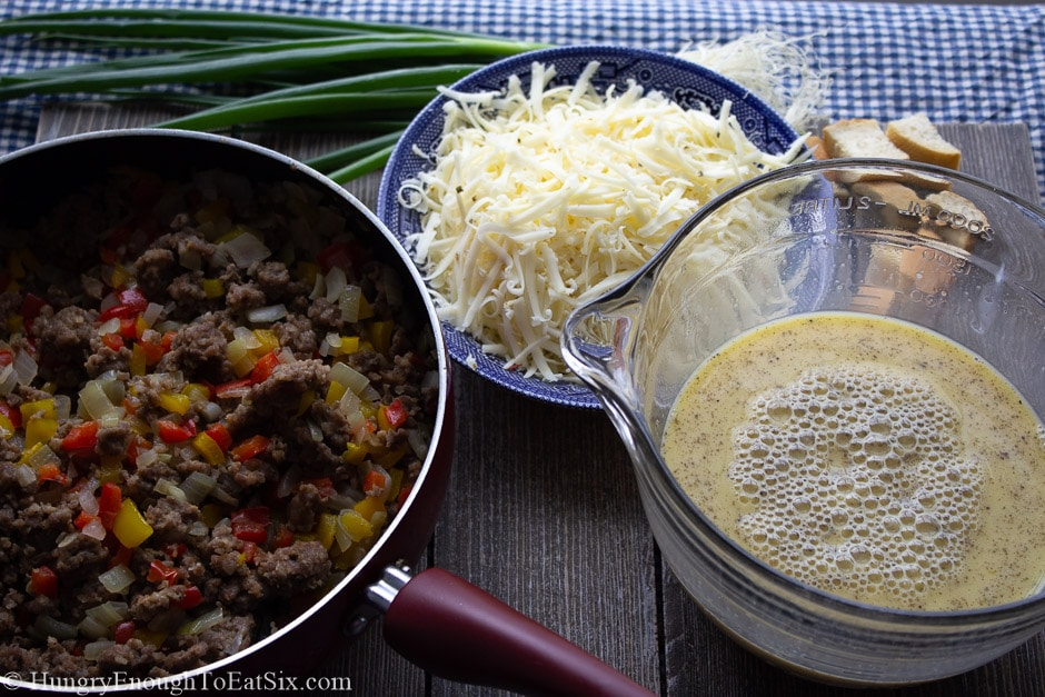Image of sauteed veggies and sausage in a pan next to shredded cheese and egg batter