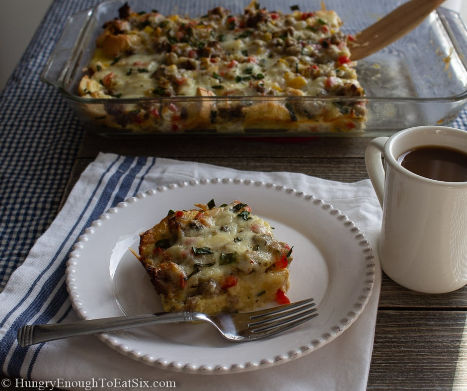 Image of a slice of Spicy Egg & Sausage Bake on a plate next to a cup of coffee