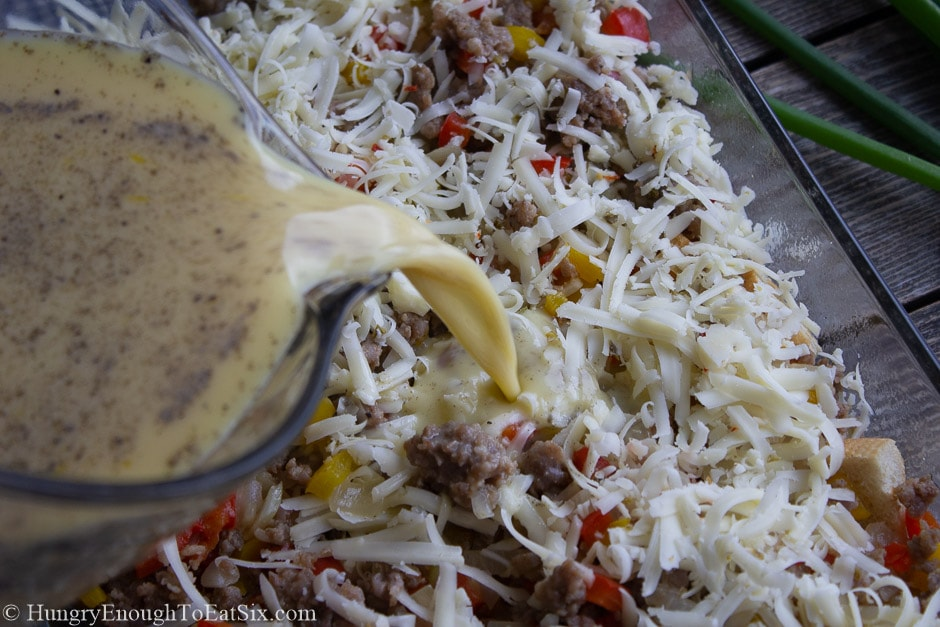 Image of egg batter pouring over pan of vegetables, sausage, and cheese.
