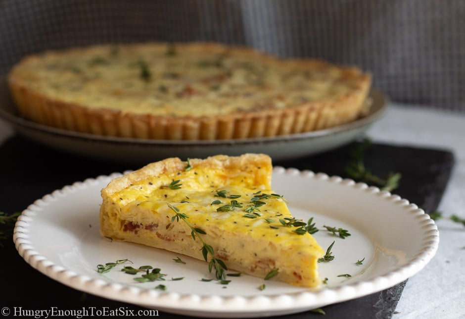 Slice of quiche Lorraine on a white plate and sprinkled with chopped thyme.