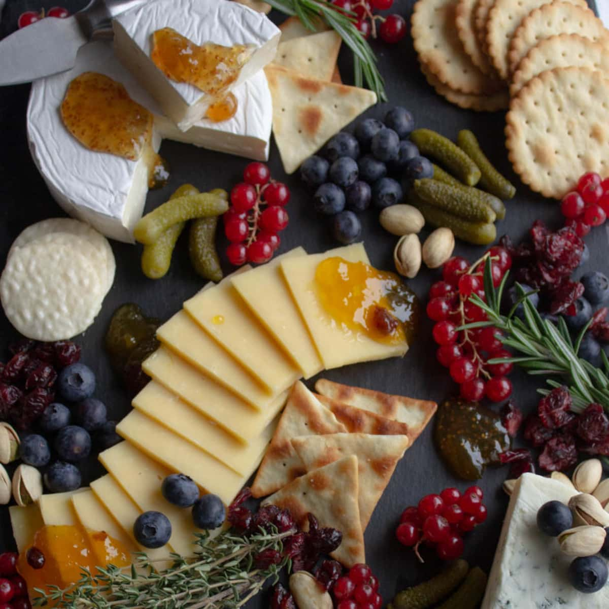 Berries, cheeses, crackers arranged on a black board