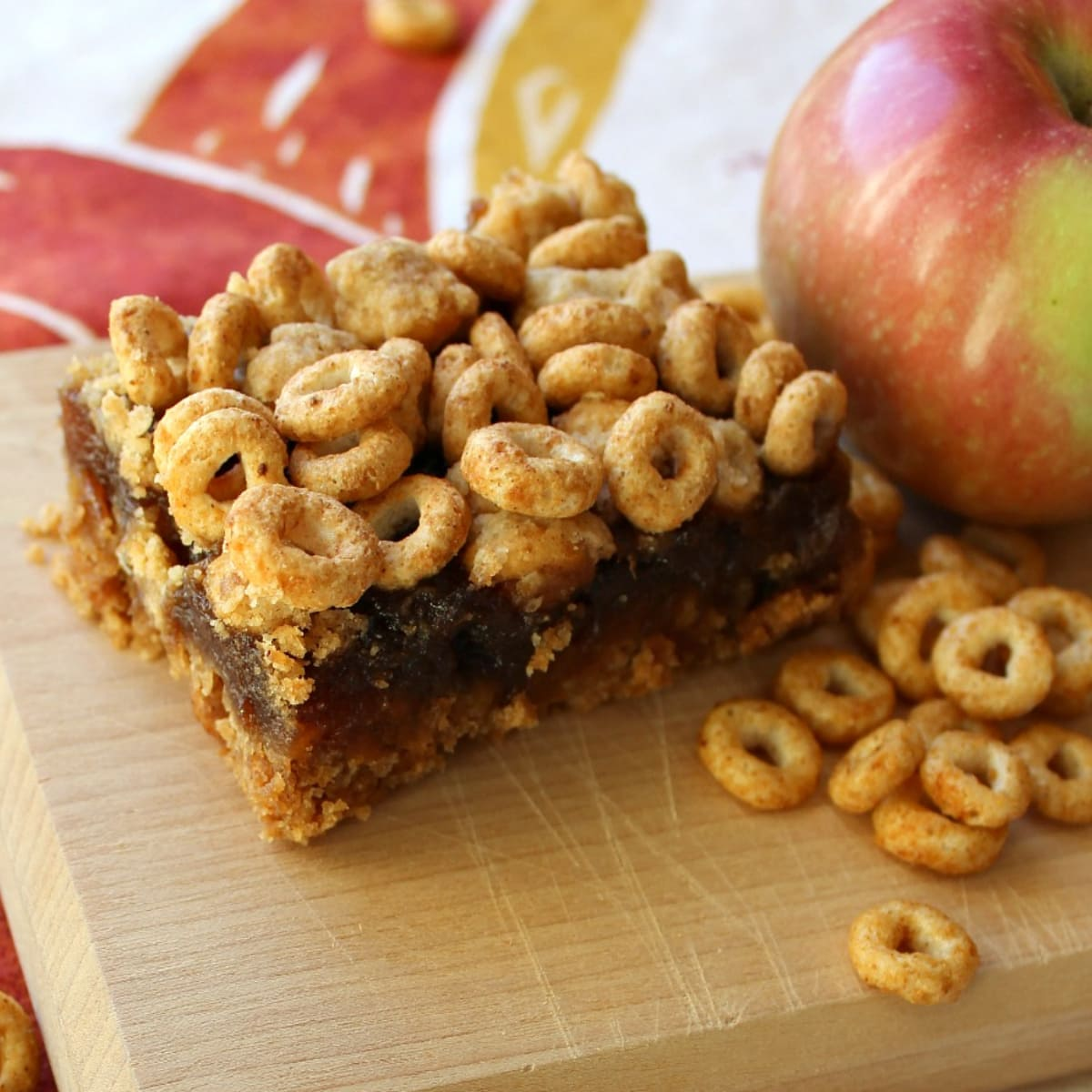 Cheerios and an apple on a board next to apple bars