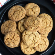 Round ginger cookies on a black plate