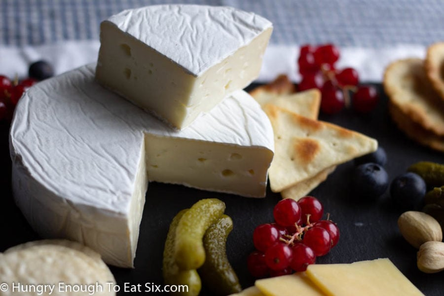 Brie wheel with a wedge cut out and stacked on top