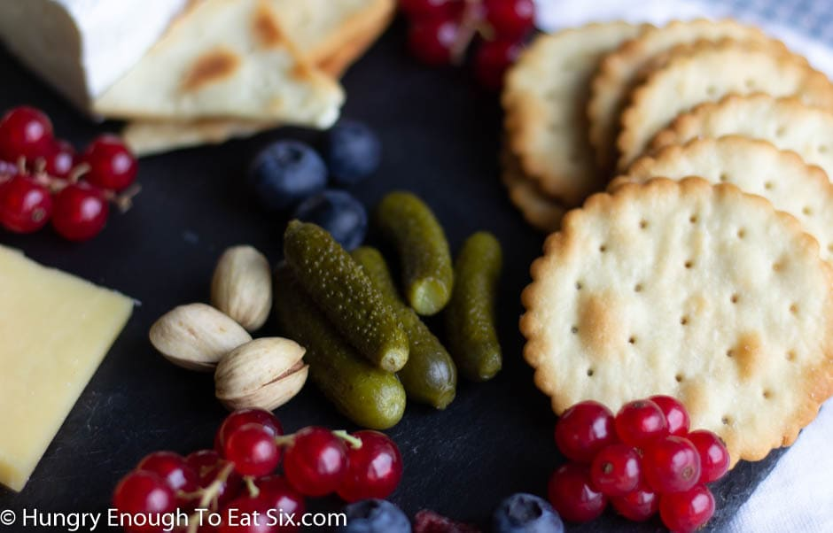 Cornichon pickles with pistachios, red currants, and crackers