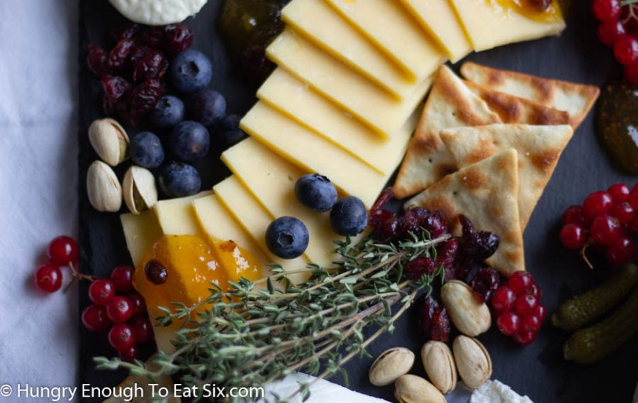 Fanned slices of cheese with blueberries, thyme sprigs, nuts, and jam.