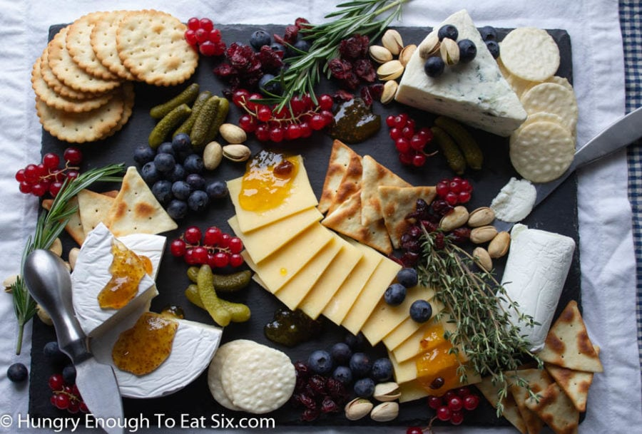 Black board with cheeses, berries, pickles, apricot jam and thyme.