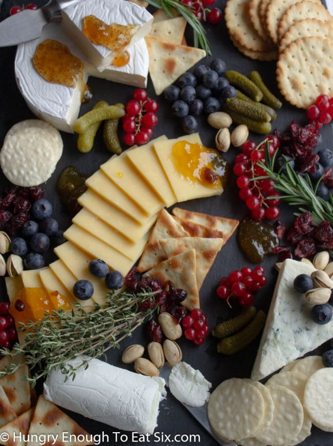 Yellow sliced cheese with red and blue berries, orange jams, white cheeses and green herbs