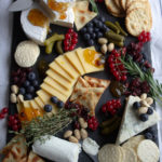 Black slate board with different cheese wedges and slices, blueberries, currants, thyme sprigs, and crackers