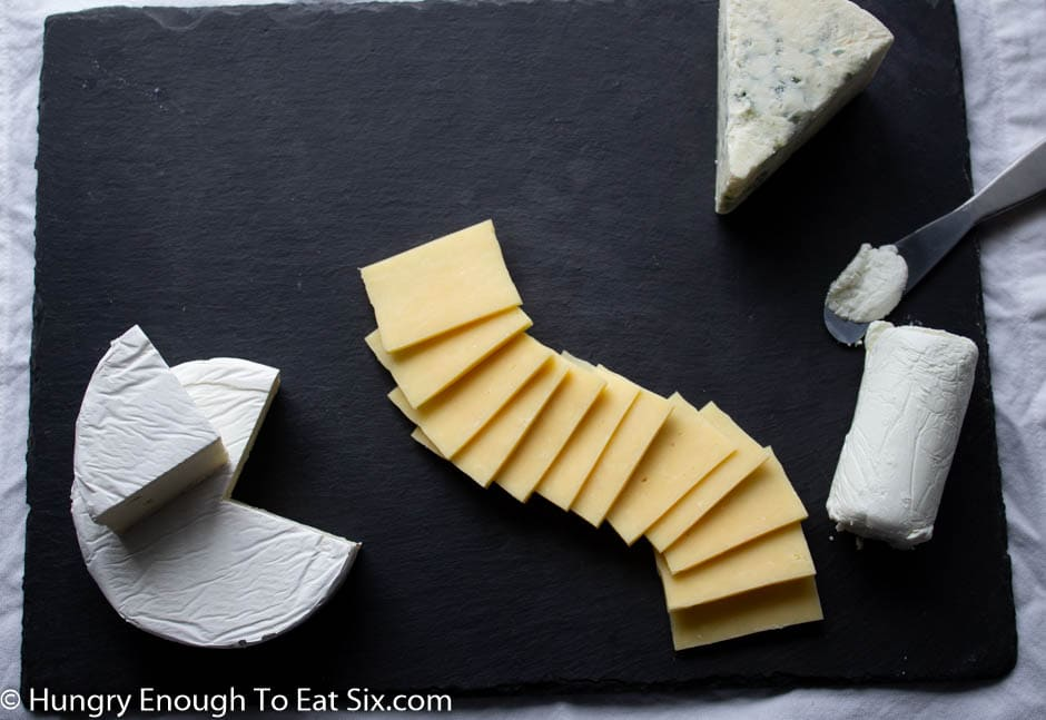 Cheese slices fanned out on a dark board.