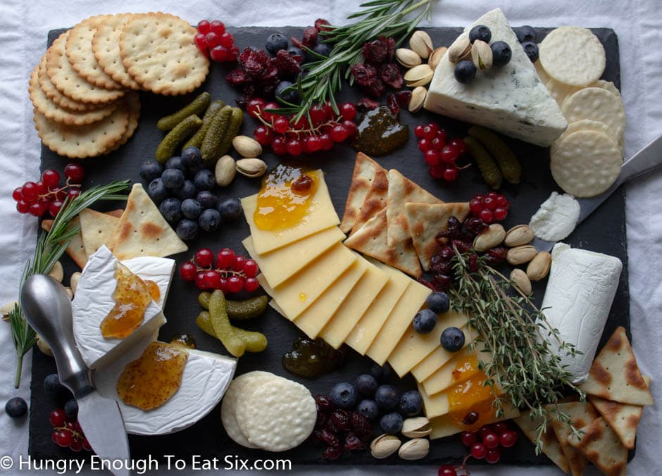 Horizontal cheese board with sliced cheeses, crackers, berries, and jam.