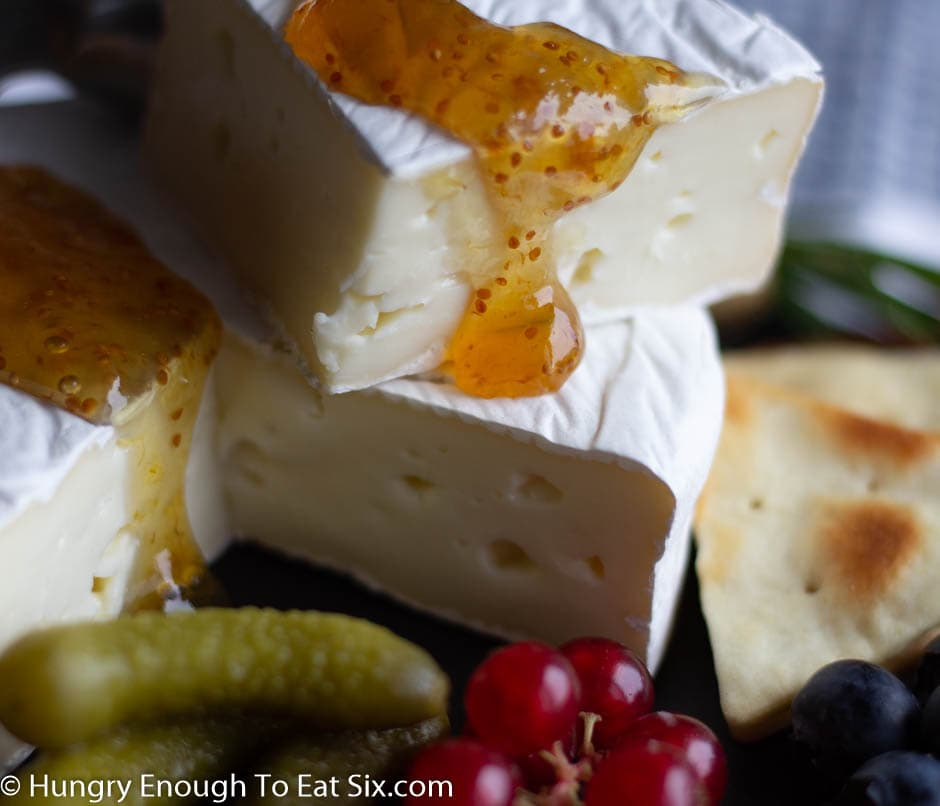 Wedges of cheese with jam dripping down the edges