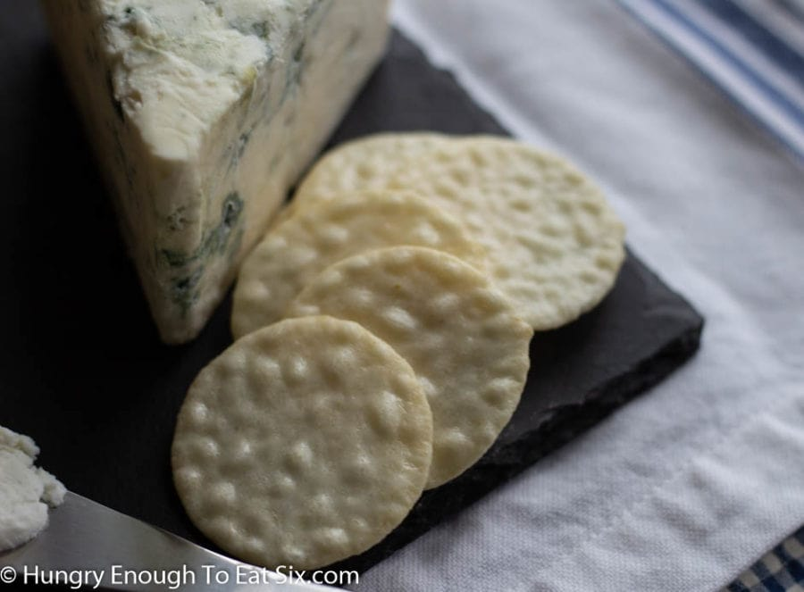 Round rice crackers next to a wedge of blue cheese