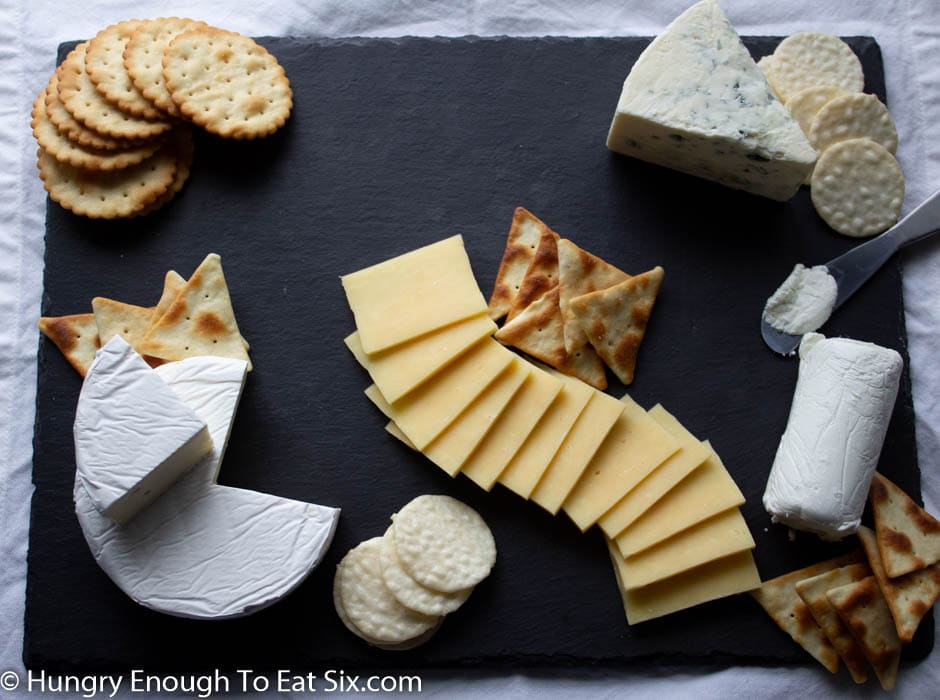 Black board with fanned cheese, brie wedges and crackers.