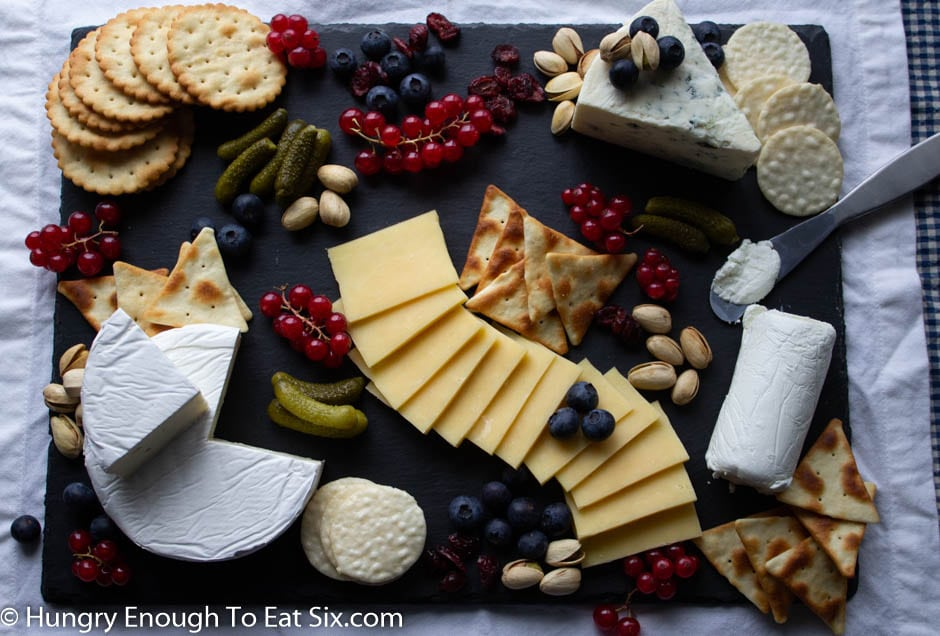 Black slate with fanned cheese slices, berries and crackers.